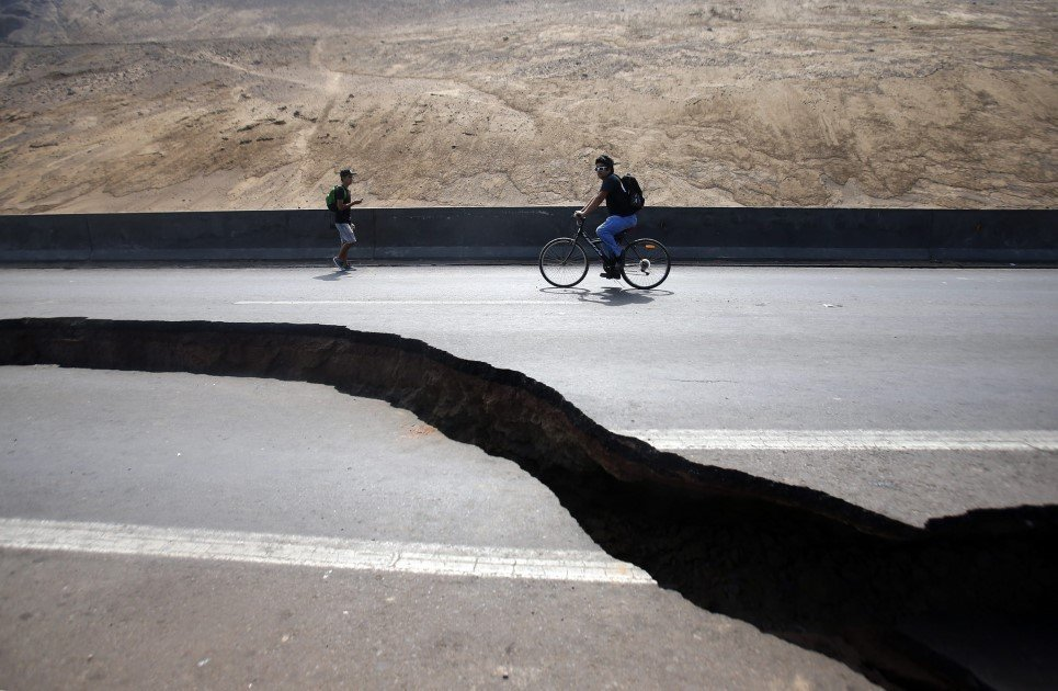 29. Two men pass by a crack in a highway between the areas of Iquique and Alto Hospicio, Chile - April 3, 2014.