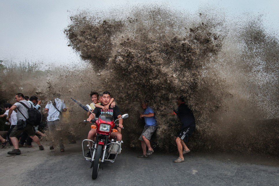 30. Visitors look to avoid a high wave hitting the bank of Qiantang River in Hangzhou, Zhejiang province, China - August 13, 2014.