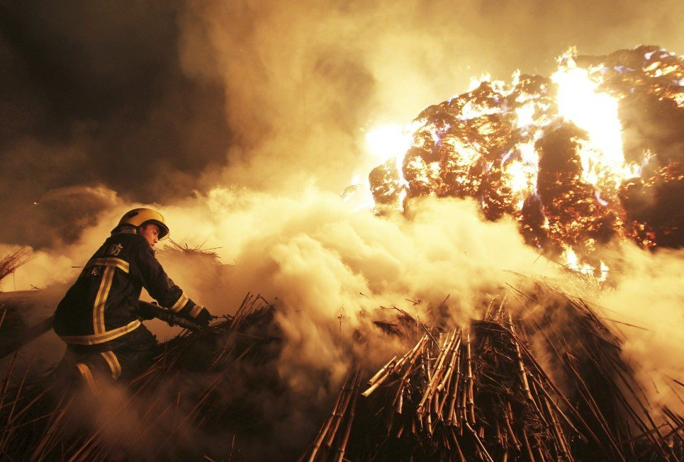 32. A firefighter attempts to extinguish a fire that broke out on piles of canes at a paper factory in Changde, Hunan province, China - February 16, 2014.
