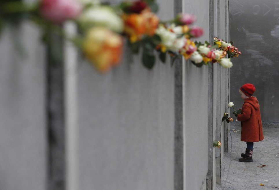41. A young girl places a rose at the Berlin Wall memorial in Bernauer Strasse, at the 25th anniversary of fall of Berlin Wall - November 9, 2014.