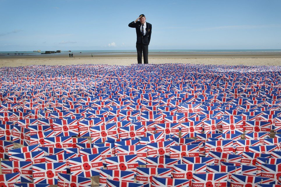 47. WWII veteran Fred Holborn, from the Fleet Air Arm, salutes as he looks at British Legion Union flags carrying thank you messages planted in the sand on Gold Beach