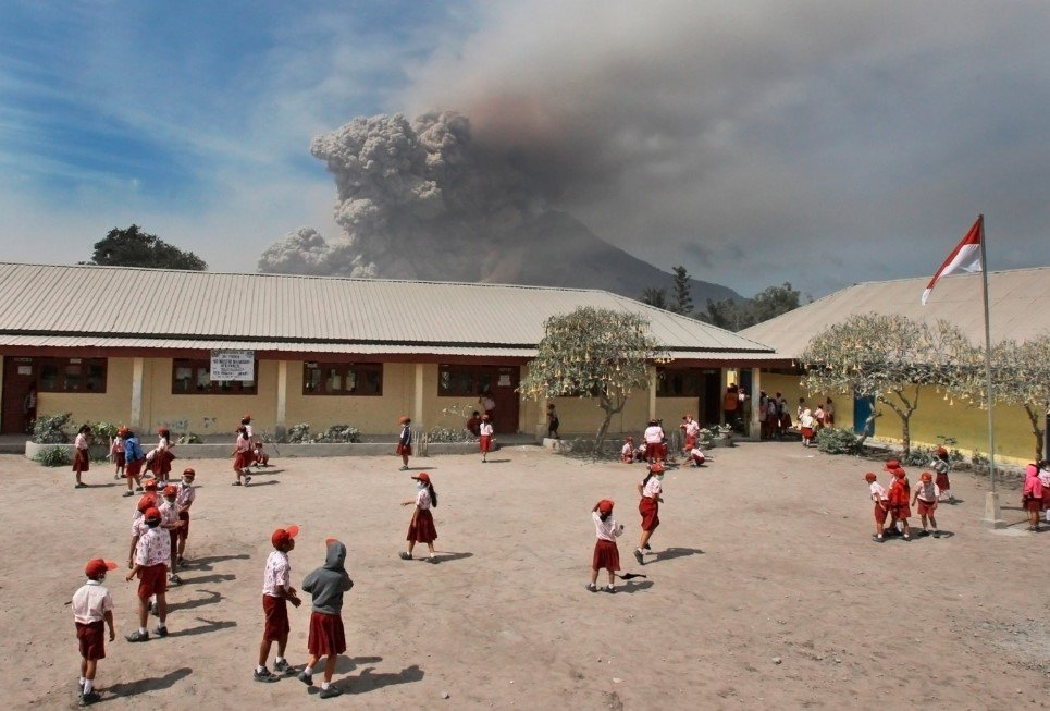 49. Students play in their school yard as Mount Sinabung erupts in Sukandebi, North Sumatra, Indonesia - January 16, 2014.