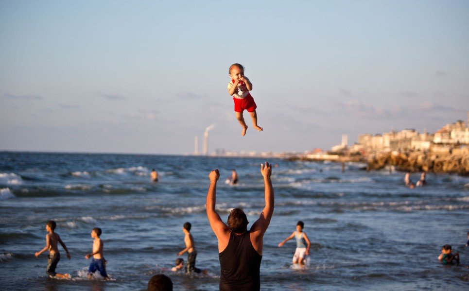 53. A Palestinian man plays with his baby on the beach of Gaza city - September 7, 2014.