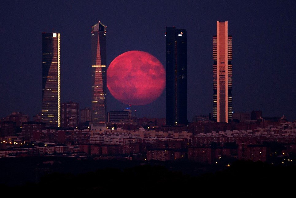 58. A spectacular super moon shines through the Four Towers Madrid skyscrapers – August 11, 2014.