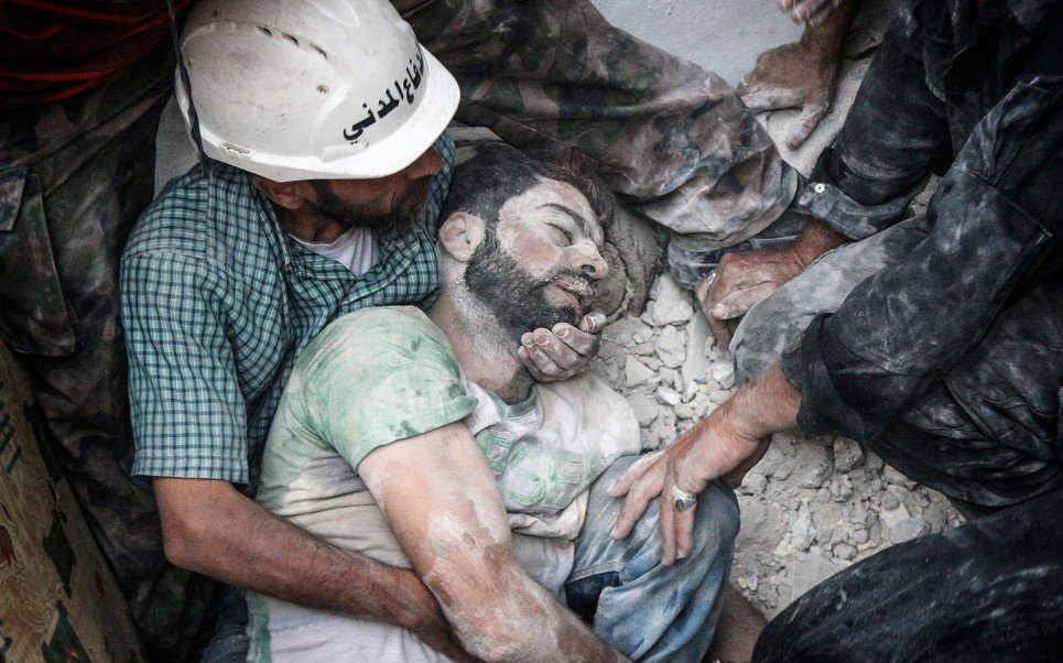 59. Search and rescue teams remove a body from the rubble after the Syrian regime shelled an opposition-controlled area of Aleppo - August 14, 2014.