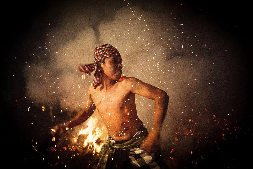 "81. A Balinese man throws a burned coconut husk during the ""Mesabatan Api"" ritual ahead of Nyepi Day Gianyar, Bali, Indonesia - March 30, 2014."