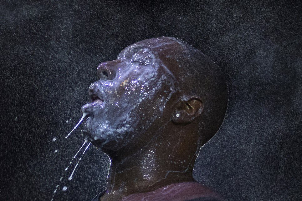 96. A man is doused with milk and sprayed with mist after being hit by an eye irritant from security forces trying to disperse protestors in Ferguson - August 20, 2014