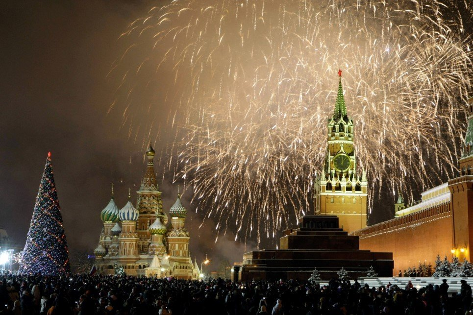 Russians celebrate the New Year on Red Square in Moscow, with the Kremlin in the background, right, and St. Basil's cathedral in background, left, Friday, Jan. 1, 2010. Tens of thousands of people gathered on the Square to celebrate the new year, and view the fireworks as the clock on the Kremlin's Spassky Tower, right, struck midnight. (AP Photo/Mikhail Metzel)