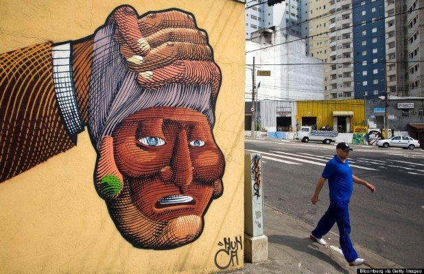 "A pedestrian walks near a painted mural by Francisco Rodrigues da Silva, known as Nunca, in the Liberdade neighborhood of Sao Paulo, Brazil, on Thursday, Aug. 7, 2008. One month after Otavio and Gustavo Pandolfo painted the river facade of London's Tate Gallery for an exhibition of street art, their hometown took gray paint to one of their 680-meter long murals to comply with a law that aims to clean up the city. Following an outcry from graffiti artists -- including the Pandolfo brothers, who are internationally recognized by the moniker ""Os Gemeos,"" or ""the twins"" -- the city government is rushing to register works of graffiti art that it will preserve."