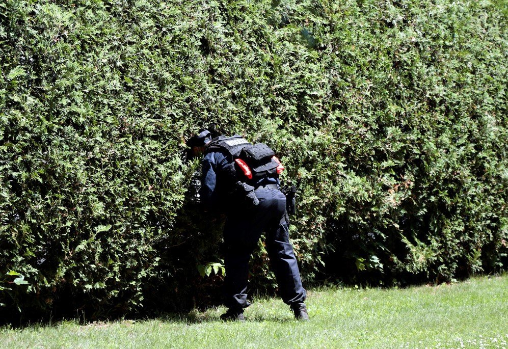 An officer checks a bush during a door-to-door search for two escaped prisoners from Clinton Correctional Facility in Malone, New York – June. 24, 2015