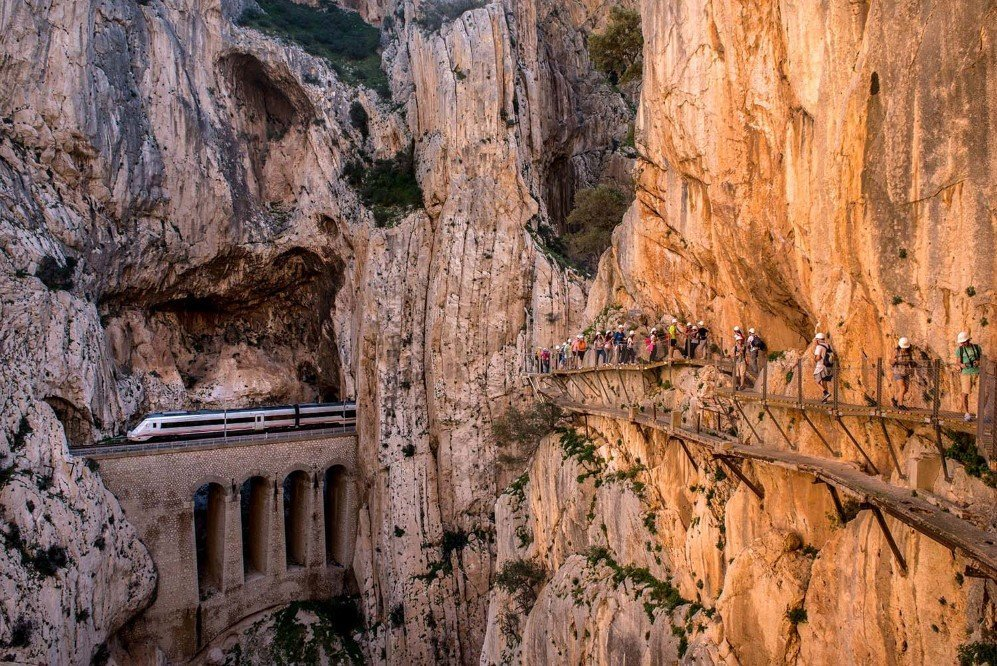 A train passes through a tunnel as tourists walk along the re-opened 'El Caminito del Rey' footpath on April 1, 2015 in Malaga, Spain. The path was built in 1905 and is known as the most dangerous walkway in the world. It was closed after two fatal accidents in 1999 and 2000. The restoration for a safer path began in 2011 and reportedly cost 5.5 million euros.