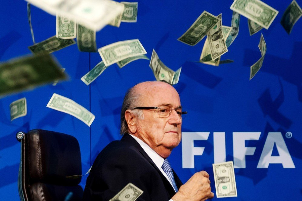 Comedian Simon Brodkin throws dollar bills at FIFA President Joseph S. Blatter during a press conference at the Extraordinary FIFA Executive Committee Meeting in Zurich, Switzerland – July. 20, 2015