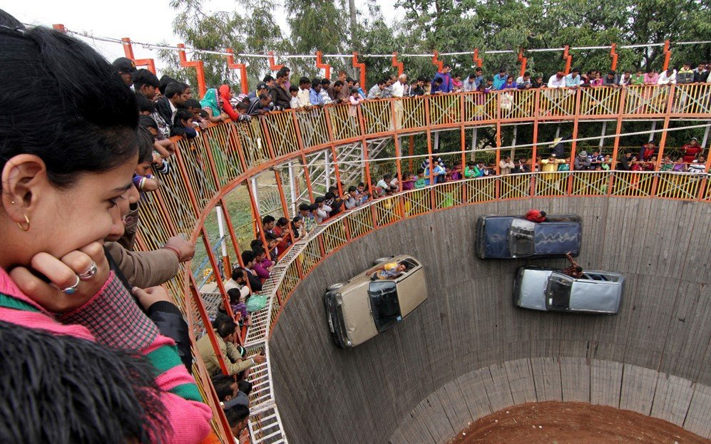 Villagers watch stuntmen performing at the show of 'Well of Death' during the annual Farmers Fair at Shama Chak Jhiri, India – Nov. 25, 2015.