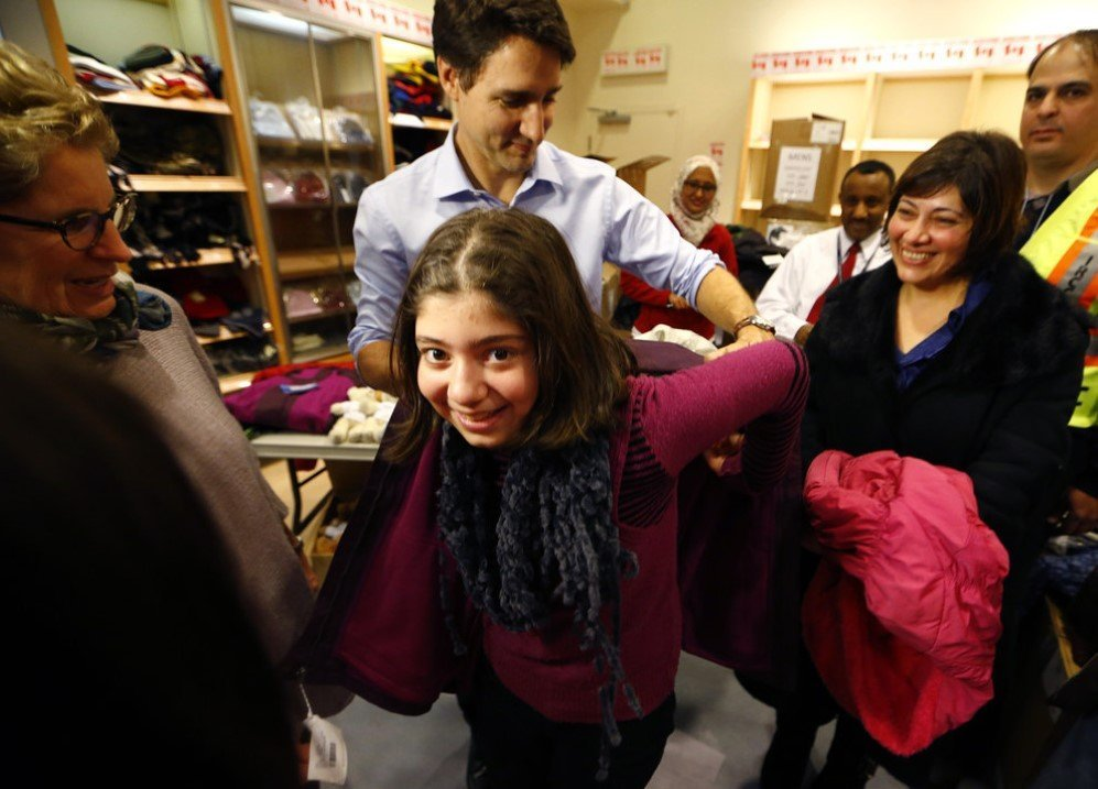 Canada's Prime Minister Justin Trudeau helps a young Syrian refugee try on a winter coat after she arrived with her family from Beirut in Mississauga, Ontario, Canada –Dec. 11, 2015