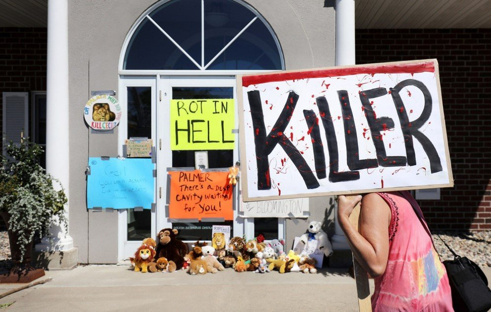 On July 29, protesters call attention to the poaching of Cecil the lion, in the parking lot of Dr. Walter Palmer's River Bluff Dental Clinic in Bloomington, Minnesota. According to reports, the 13-year-old lion was lured out of a national park in Zimbabwe and killed by Palmer, who had paid at least $50,000 for the hunt.