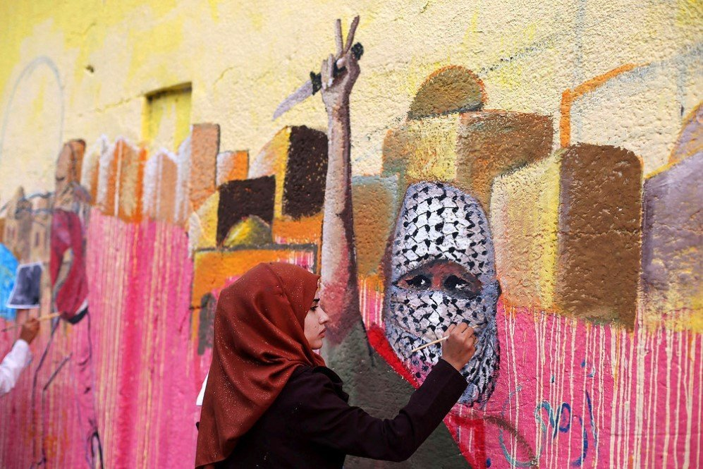 A Palestinian woman painting a mural in support of Palestinians committing stabbing attacks against Israelis –Nov. 3, 2015.