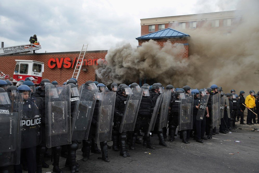Baltimore police form a perimeter around a CVS pharmacy that was plundered and torched during the riots – April 27, 2015.