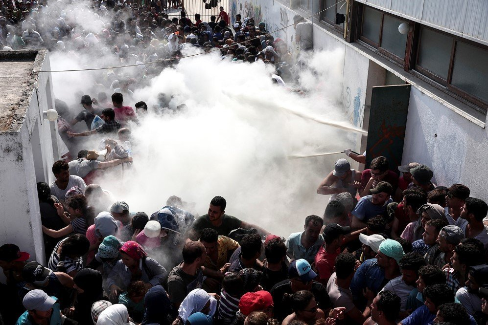 Policemen spray fire extinguishers to disperse hundreds of refugees in Kos, Greece – Aug. 11, 2015.