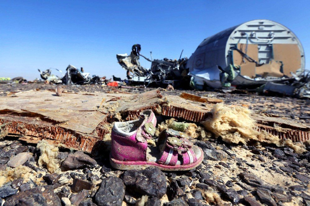 A child's shoe is seen in front of debris from a Russian airliner that crashed at the Hassana area in Arish city, north Egypt killing all 224 people onboard. – Nov. 1, 2015