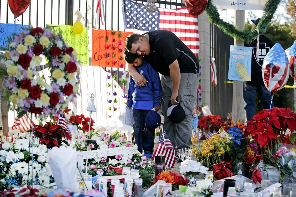Father and son pay their respects at a makeshift memorial site to honor the shooting victims in San Bernardino, California – Dec. 9, 2015