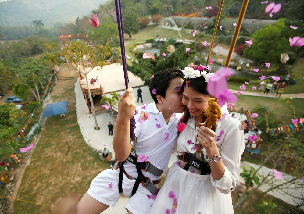 Newly married Thai couple is suspended from ropes during their rock climbing wedding ceremony in Thailand – Feb. 13, 2015.