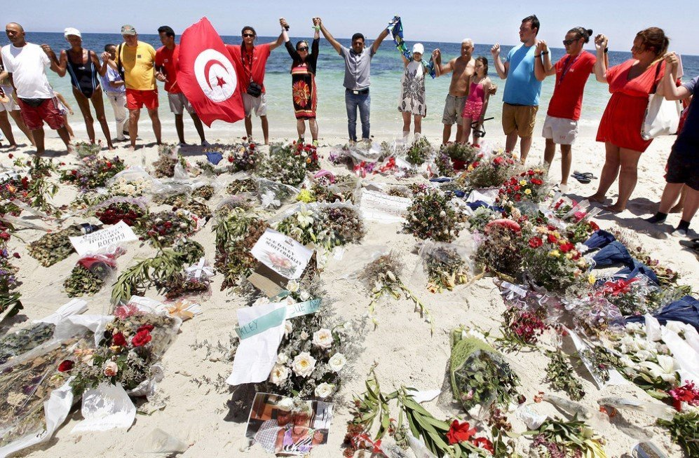 People join hands as they observe a minute's silence in memory of those killed in an attack at a beach in Sousse, Tunisia – July 3, 2015