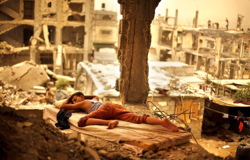 A Palestinian boy is found sleeping on a mattress inside the remains of his family's house that was destroyed by Israeli shelling during a 50-day war in 2014 – Sept. 8, 2015.
