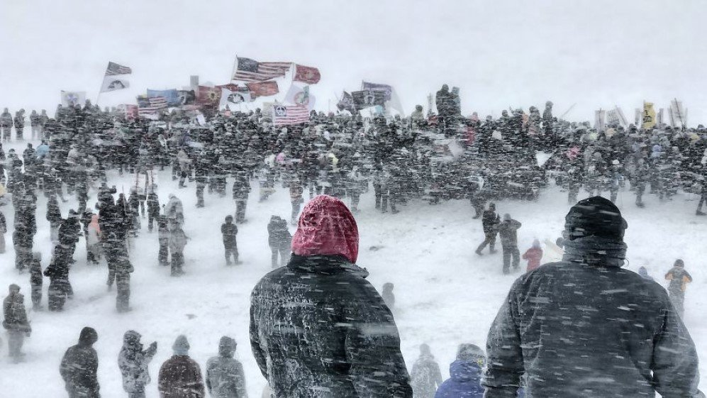 These pictures were taken on December 5th, 2016 at Standing Rock, North Dakota. That day the water protectors, the people standing up for the Sioux tribe were supposed to get evicted by the Morton County Sheriff's Department. Thousands of veterans came to the aid of those of us who were protesting. They told us that they had vowed to protect this country from all enemies, foreign and domestic. President Obama announced that the Dakota Access Pipeline had to be halted until an investigation was made. The veterans still marched on that afternoon and made sure to let everyone know that they were there helping protect Standing Rock. Mother Nature stepped in that day with a blizzard of 40 to 50 mph winds with temperatures of -30F. The height of the storm and the march was captured with the photo that was selected for first place. Everyone there stood until it was physically impossible to continue. Shortly after that picture was taken everyone had to go back to camp and the officers on the other side of the bridge had to leave as well. It was a great reminder of who truly was in charge.