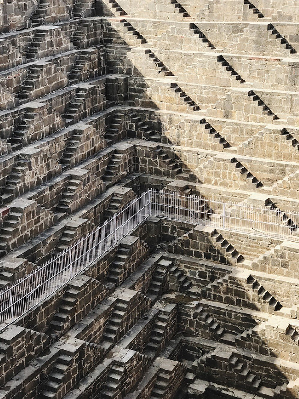 This photo was taken when I was traveling in India. Chand Baori consists of 3,500 narrow steps over 13 storeys. It extends approximately 30 meters into the ground making it one of the deepest and largest stepwells in India. I marveled these elegant stepwells and shadows, I immediately took out my camera and captured this beautiful scene before it was gone.