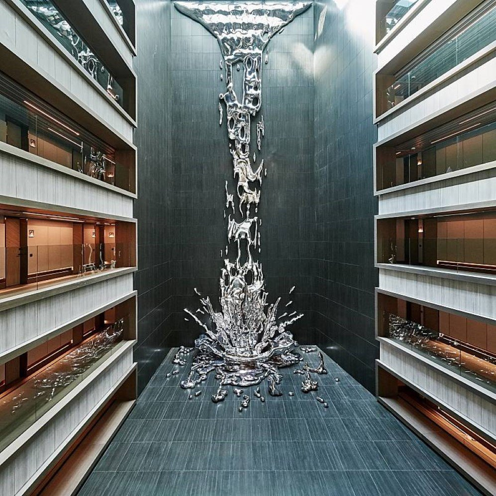 this metallic waterfall sculpture descends straight through the