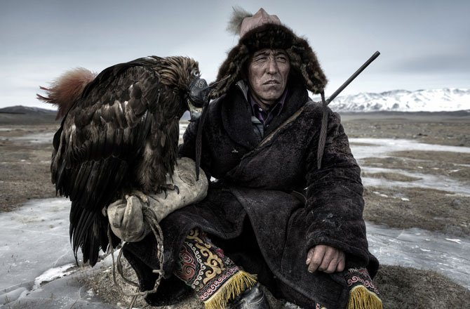23.Above, a hunter rests on the plains (in) Western Mongolia with his eagle. (Simon Morris/2014 Sony World Photography Awards)