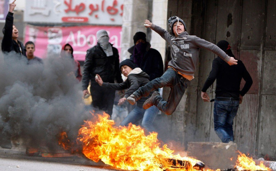 23. A Palestinian boy throws a stone towards Israeli soldiers as he jumps over burning tyres - March 17, 2014.