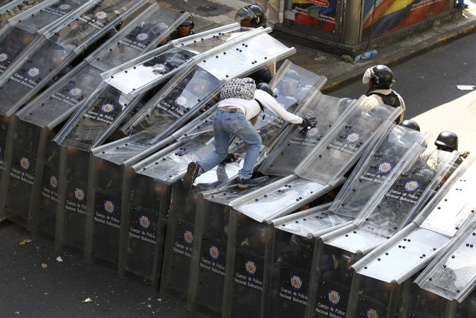 40. A protestor jumps on a shield wall formed by riot police during a protest against Venezuela's President Nicolas Maduro's government in Caracas - February 12, 2014.