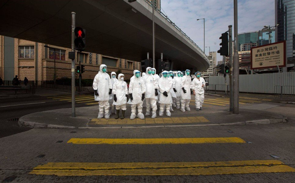 44. Health officers in full protective gear wait to cross a road near a wholesale poultry market in Hong Kong - January 28, 2014.