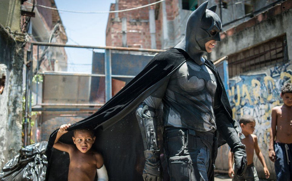 56. Children play around a man disguised as Batman at the Favela do Metro slum, in Rio de Janeiro, Brazil - January 9, 2014.