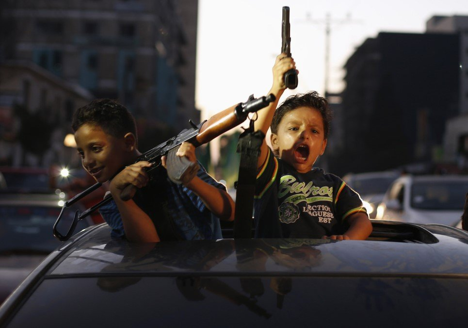 62. Palestinian children hold guns as they celebrate after a ceasefire in Gaza City - August 26, 2014.