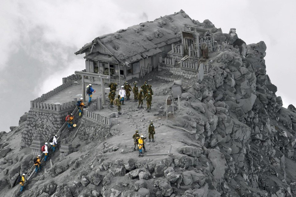85. Rescue workers climb to an ash-covered shrine near the summit of Mt. Ontake, Japan, which erupted and killed 56 people.