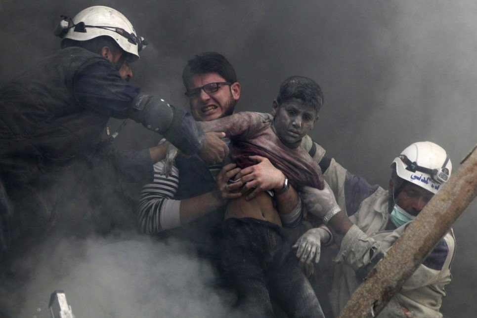 89. Men rescue a boy after forces loyal to Syria's President Bashar Al-Assad bombed Aleppo - April 6, 2014.