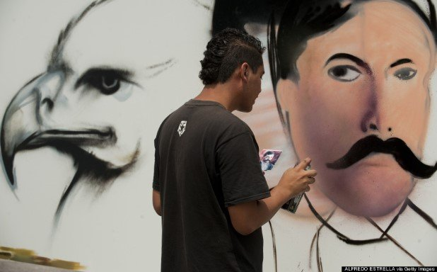 An artist works on his graffiti painting
