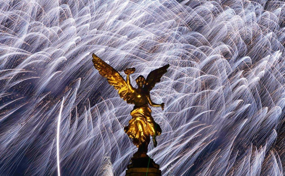 Mexico's golden Angel of Independence stands in front of fireworks during New Year's celebrations in Mexico City, Tuesday, Jan. 1, 2008. (AP Photo/Gregory Bull)