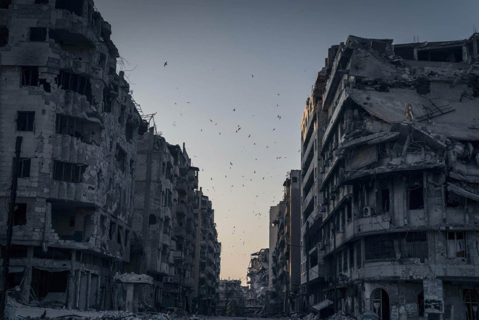 Birds fly over the destroyed houses in Khalidiya district in Homs, Syria. In the vast stillness of the destroyed city center of Homs, there are large areas where nothing moves. Then, suddenly, wind blows a ripped awning, or birds fly overhead.