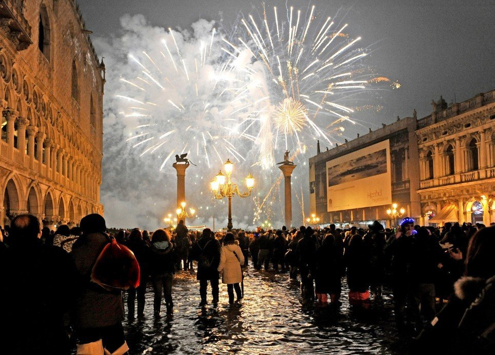 People watch New Year's Eve fireworks over Venice's St. Mark square flooded by high water, early Friday, Jan. 1, 2010. The phenomenon of high water, which floods the Venice lagoon, occurs mainly between autumn and spring when tides are reinforced by seasonal winds. (AP Photo/Luigi Costantini)