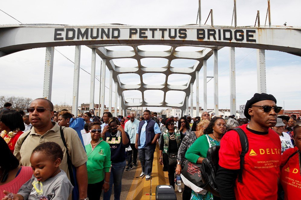 Thousands of people march across the Edmund Pettus Bridge during the 50th anniversary of the civil rights march in Selma, Alabama – March 8, 2015.