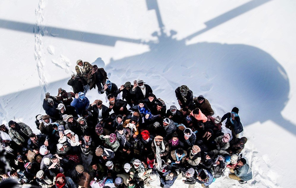 Survivors of an avalanche looking up to an army helicopter for relief goods in Paryan district of Panjshir province, Afghanistan – Feb. 28, 2015
