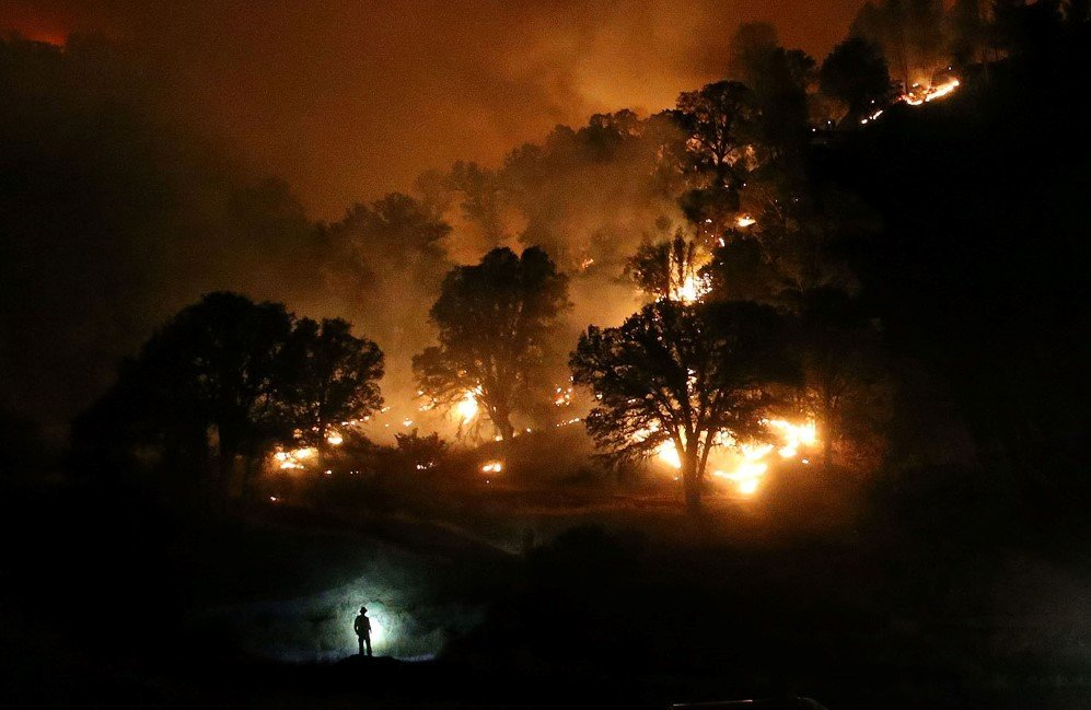 A California firefighter monitors a backfire while battling the Rocky Fire near Clearlake, California. The Rocky Fire burned more than 60,000 acres – Aug. 3, 2015