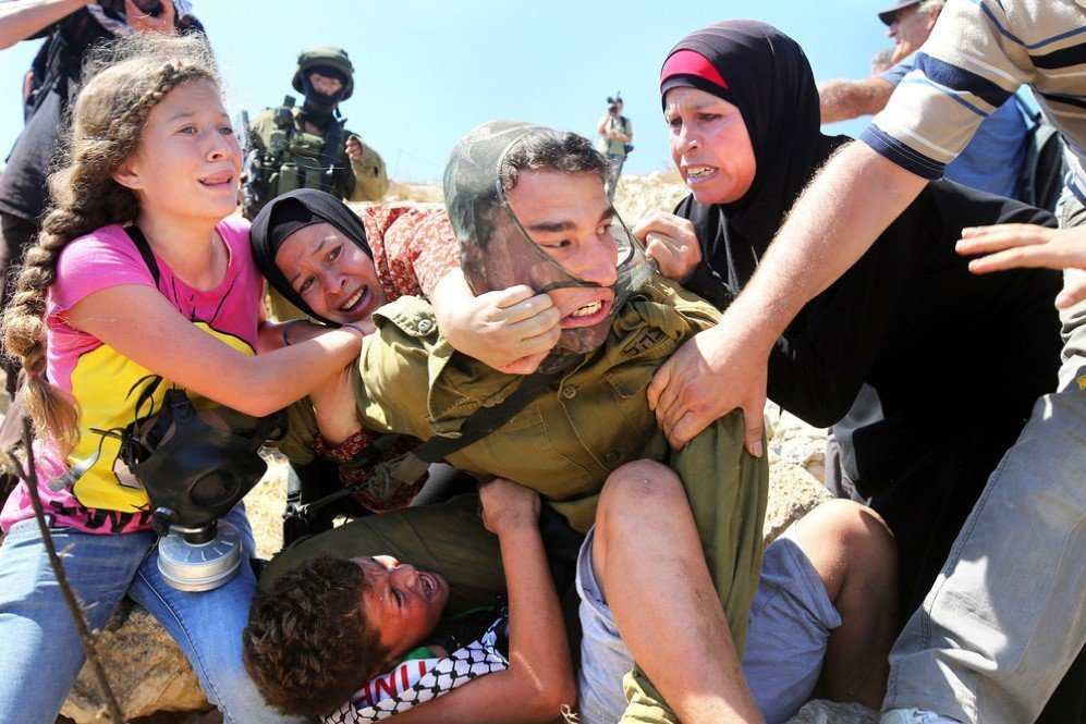 Palestinians fight to free a Palestinian boy held by an Israeli soldier during clashes between Israeli security forces and Palestinian protesters – Aug. 28,2015