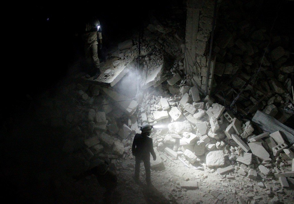 Search and rescue teams inspect collapsed buildings after Assad regime forces attacked a residential area in Aleppo, Syria – July 9, 2015.