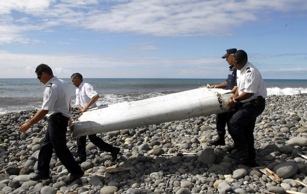 Officers carry a plane part that apparently washed ashore in on Reunion Island. French officials determined on Sept. 3, 2015 that it came from missing Malaysian Airlines Flight 370. No other debris has been found since, and the disappearance remains a mystery.