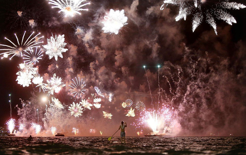 A man rides a stand up paddle board as fireworks explode above him during New Year's festivities on Copacabana Beach, Rio de Janeiro, Brazil – Jan. 1, 2015