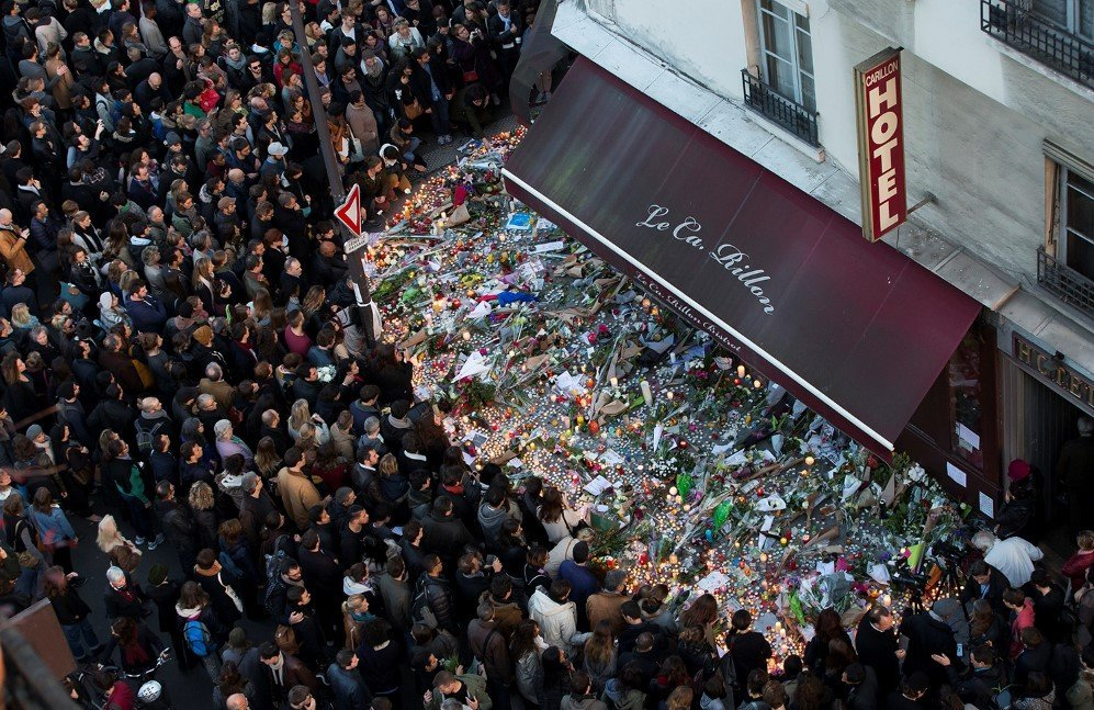 A large crowd gathers to lay flowers and candles in front of the Carillon restaurant after the Paris attacks – Nov. 15, 2015.